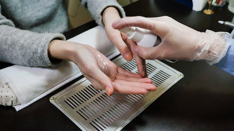Desinfectie van de cliënt` s handen Vrouwen` s handen bij manicureprocedures royalty-vrije stock foto