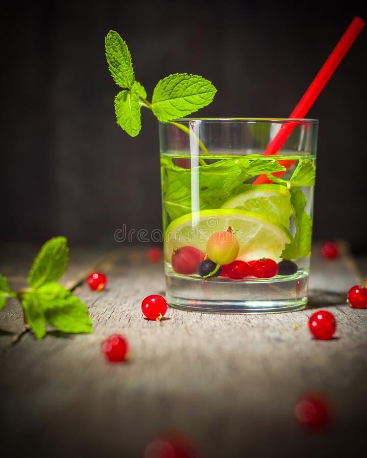 Desintoxicação da água em uma taça de vidro Hortelã e bagas verdes frescas Um refrescamento e uma bebida saudável fotografia de stock royalty free
