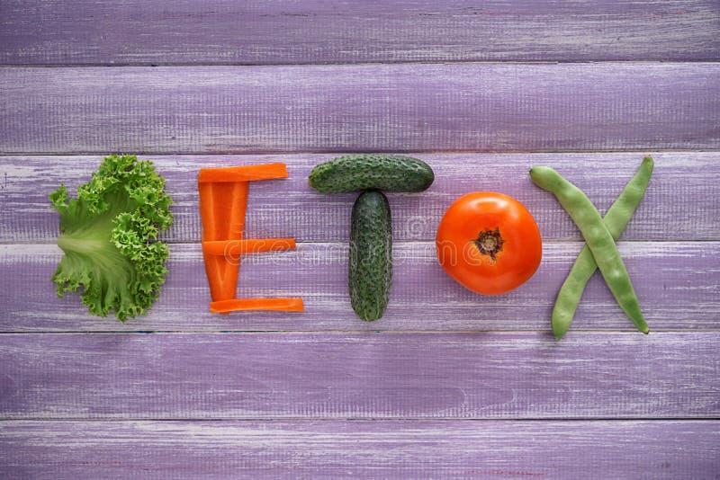 DESINTOXICAÇÃO da palavra feita de vegetais saudáveis no fundo de madeira Fa?a dieta o conceito fotografia de stock royalty free