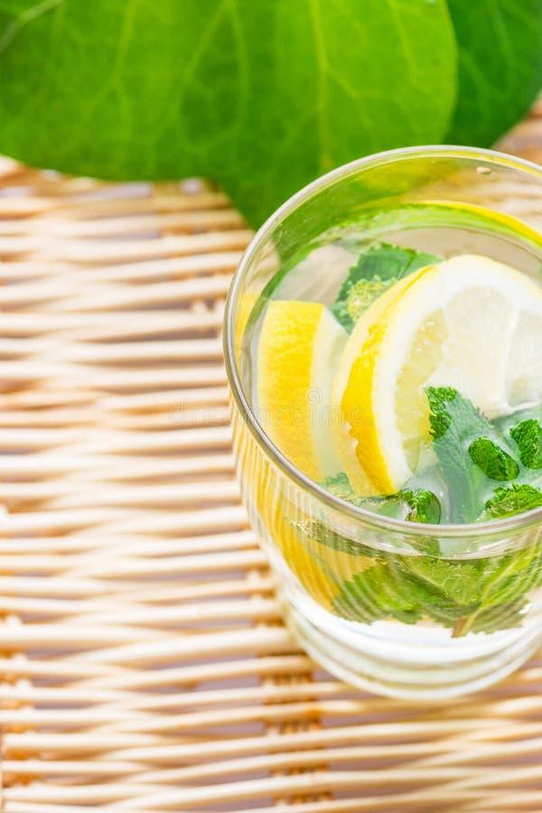 A desintoxicação de refrescamento infundiu a água sassy com o gengibre da hortelã fresca do limão no vidro na tabela de vime com  fotografia de stock royalty free