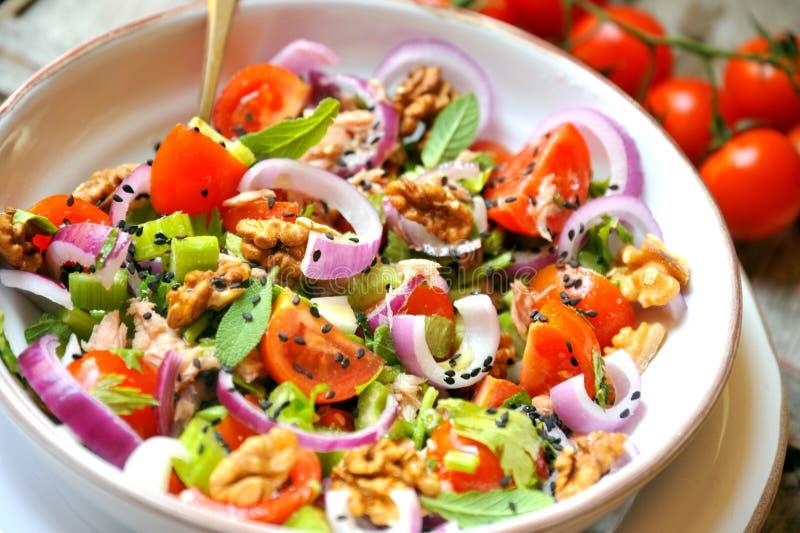 Desintoxicação, vegetariano, salada crua com tomate, cebolas e nozes fotografia de stock