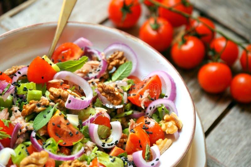 Desintoxicação, vegetariano, salada crua com tomate, cebolas e nozes fotos de stock royalty free