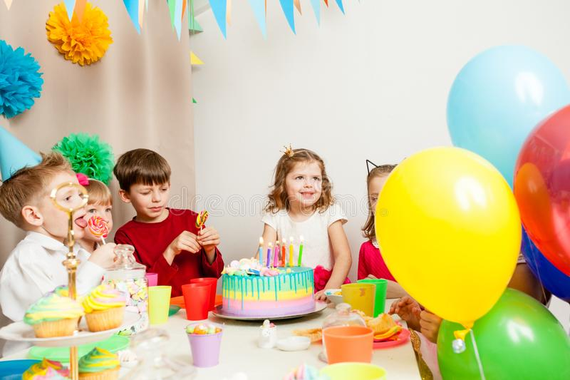 Desire on birthday. Little kids celebrating birthday. The girl makes a wish before blowing candles on the cake royalty free stock image