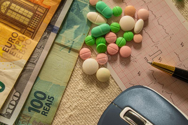 Desk with bills and medicines. Concept of cost of health and drug addiction stock images