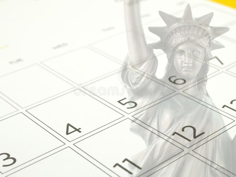White desk calendar page with days and dates in July 2017 and part of faded bronze metal statue of liberty national monument. Close up white desk calendar page royalty free stock image