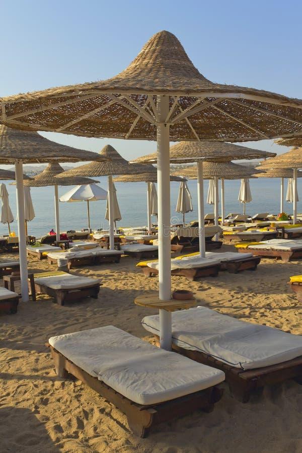 Desk chairs and umbrella on a beach stock photos