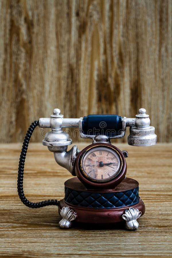 Desk Clock with Antic Telephone Shape on Brown Background. Desk clock with antic telephone shape on brown wooden background stock images