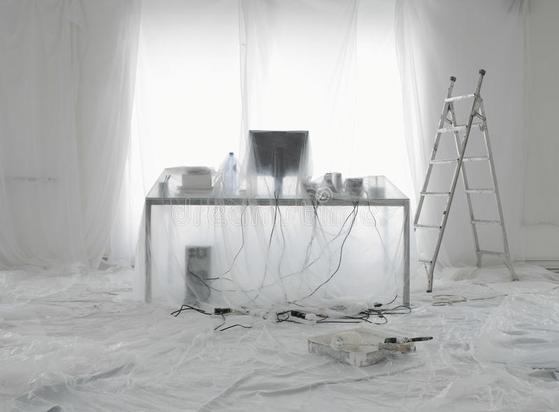 Desk And Computer Covered In Transparent Dust Sheets stock photography