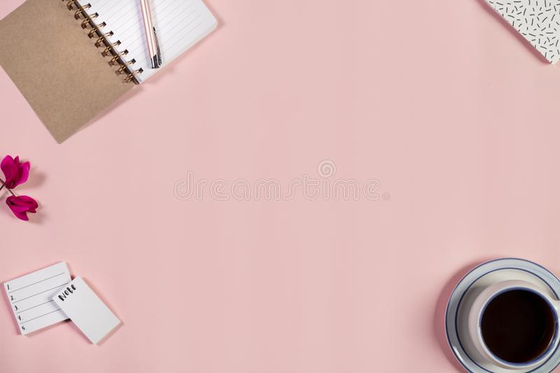 Desk with cup of coffee, notepad and pen on baby pink background. Top view. stock image
