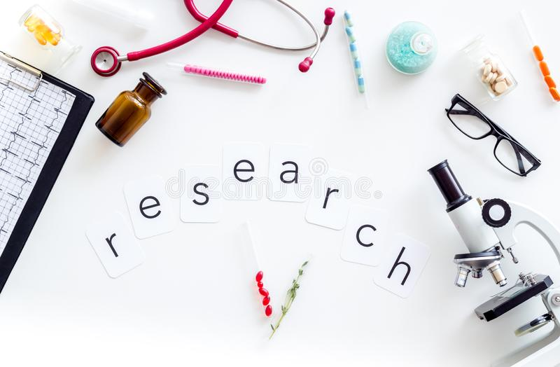 Do medical research with microscope, stethoscope, cardiogram, pills and test tube on white background top view. Desk of doctor. Do medical research with royalty free stock photos