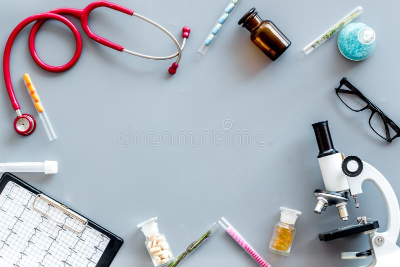 Do medical research with microscope, stethoscope, pad, pills and test tube on gray background top view mock up. Desk of doctor. Do medical research with stock images