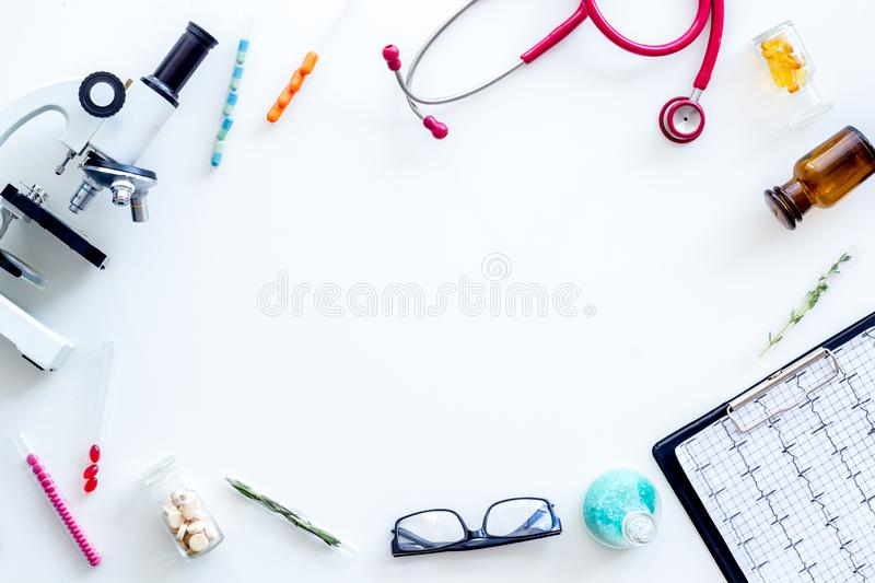 Do medical research with microscope, stethoscope, pad, pills and test tube on white background top view mock up. Desk of doctor. Do medical research with stock photography