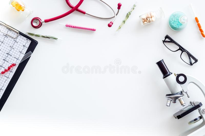 Do medical research with microscope, stethoscope, pad, pills and test tube on white background top view mock up. Desk of doctor. Do medical research with royalty free stock images