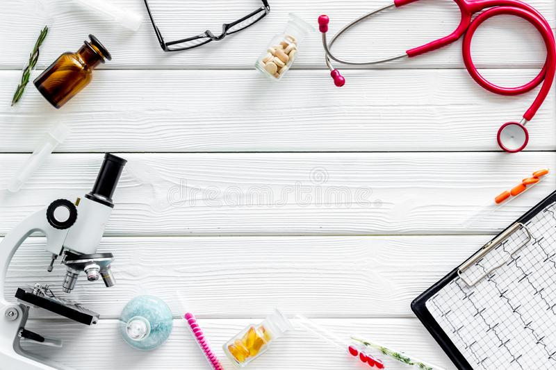 Do medical research with microscope, stethoscope, pad, pills and test tube on white wooden background top view mock up. Desk of doctor. Do medical research with royalty free stock photos