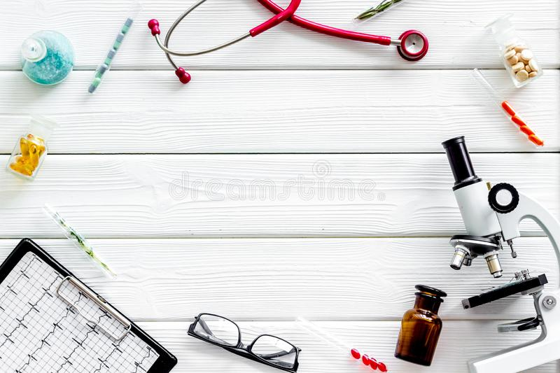 Do medical research with microscope, stethoscope, pad, pills and test tube on white wooden background top view mock up. Desk of doctor. Do medical research with stock images