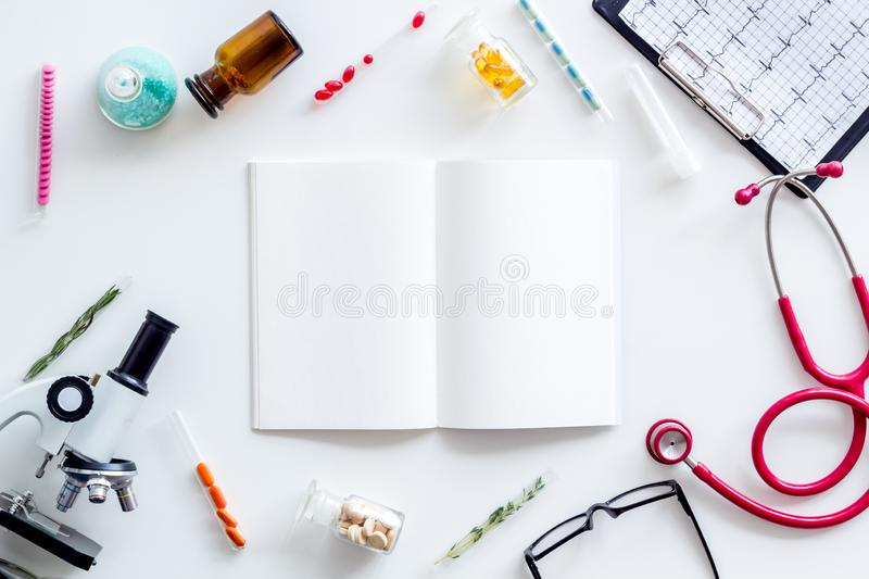 Medical research with notebook, microscope, stethoscope, cardiogram, test tube frame on white background top view mockup. Desk of doctor in laboratory. Medical royalty free stock image
