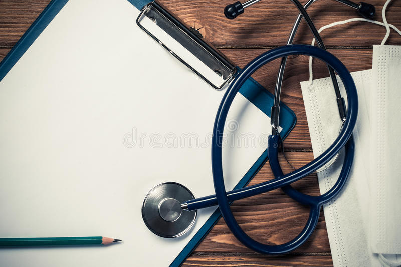 Desk of doctor with medicine things. Doctors wooden table with tablet stethoscope and other stuff stock photos
