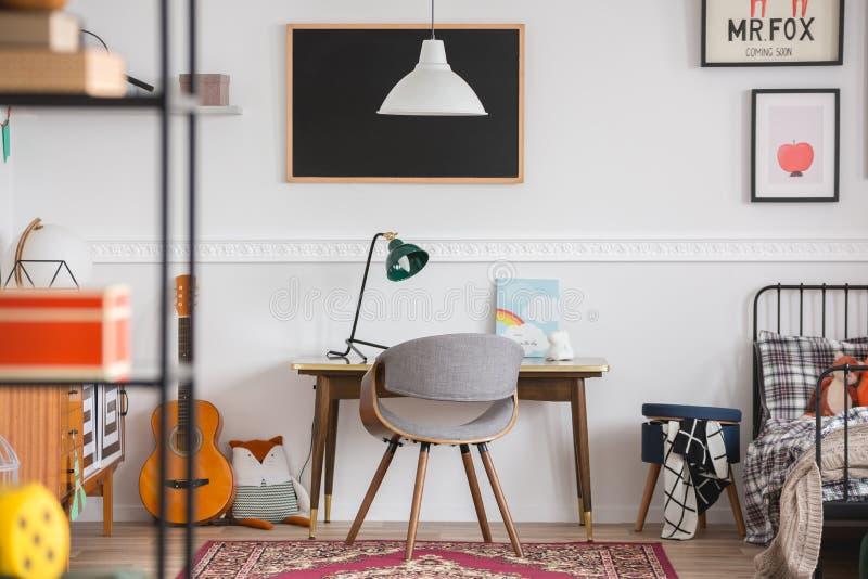 Desk en stoel in de werkruimte in de kinderkamer van het oude geslacht stock fotografie
