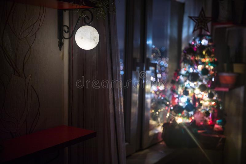 desk of free space and lamp with xmas tree in home . Christmas lantern in selective focus near window with holiday tree full of stock image