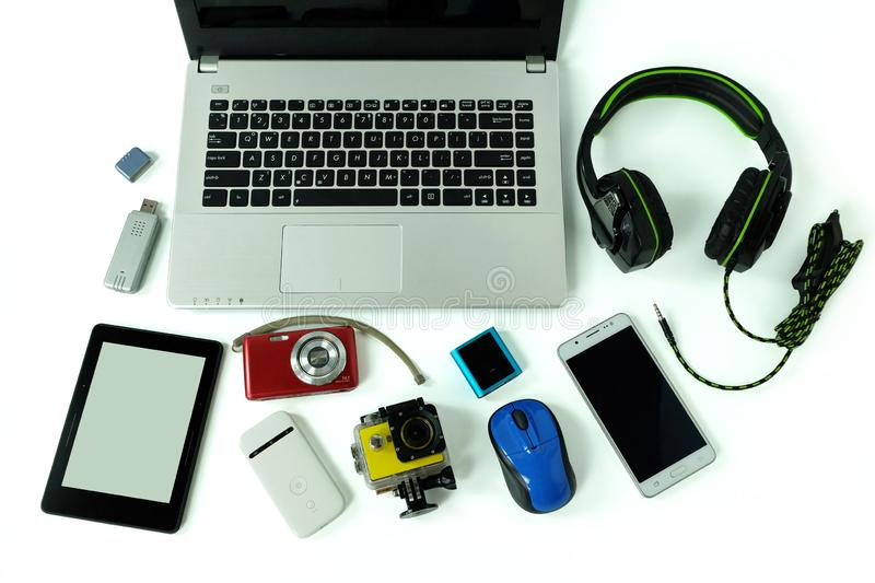 Desk with gadgets or electronic equipment for daily use, laptop computer, cell phones and digital camera royalty free stock images