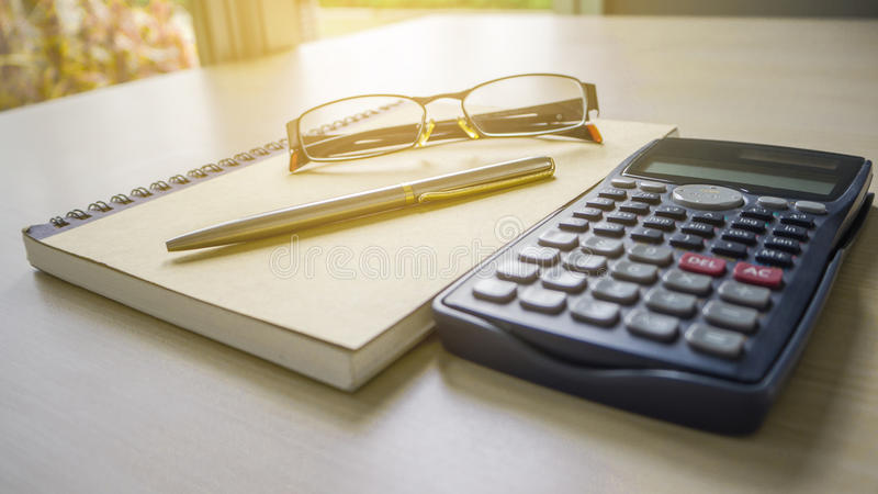 The desk have empty notebook, eyeglasses and calculator. On the wooden table stock photography