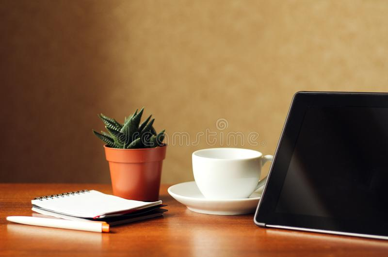 Desk at home office. Black tablet, indoor flower and notepad on a wooden table. Concept - work at home, freelancer.  stock image