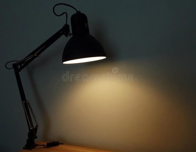 A desk lamp with the light on. royalty free stock images