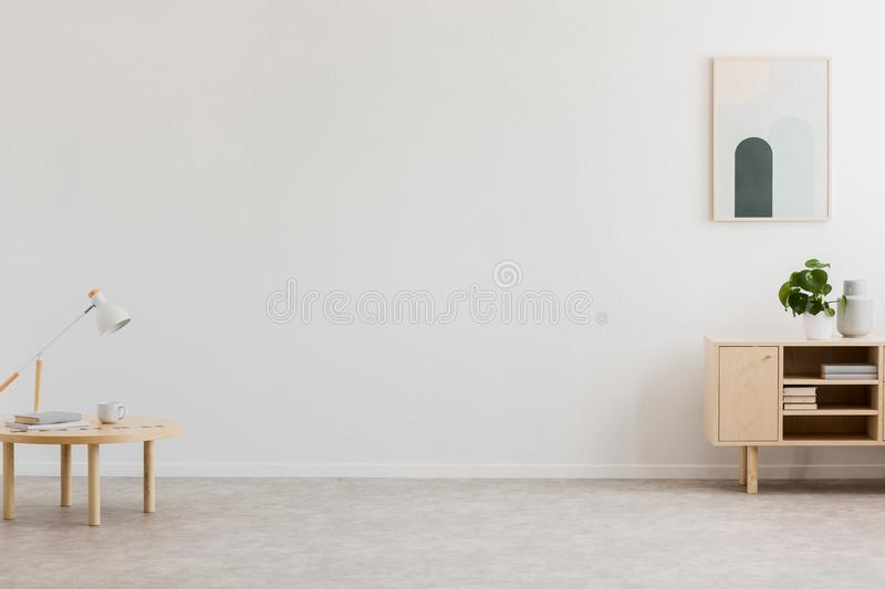 Desk lamp on a small table and a simple, wooden cabinet in an empty living room interior with white wall and place for a sofa. Rea stock images