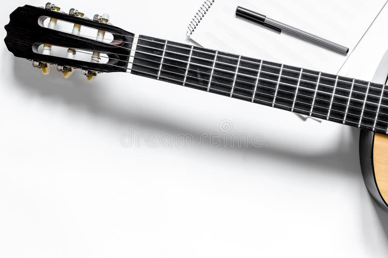 Desk of musician for songwriter work set with guitar and paper white background top view mockup royalty free stock photo