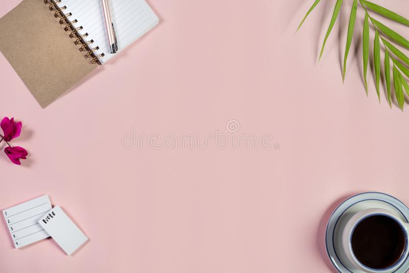 Desk with notepad, cup of coffee and pen on baby pink background. Top view. royalty free stock photos