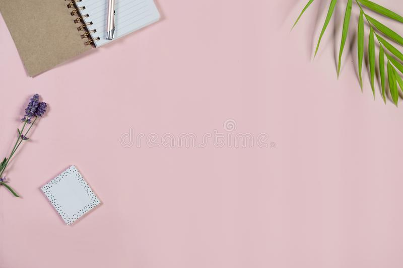 Desk with notepad and pen on baby pink background. Top view. stock photos