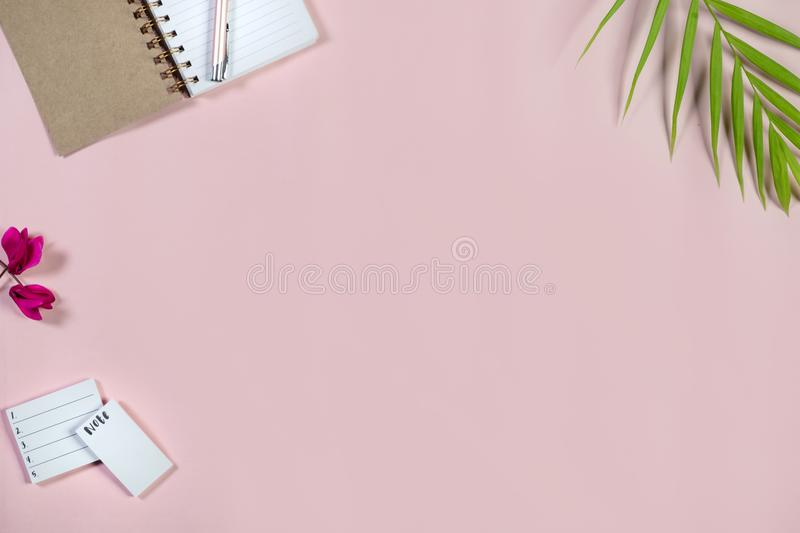 Desk with notepad and pen on baby pink background. Top view. royalty free stock photography