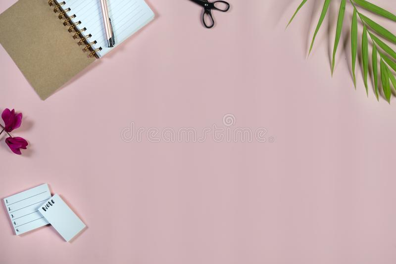 Desk with notepad and pen on baby pink background. Top view. royalty free stock image