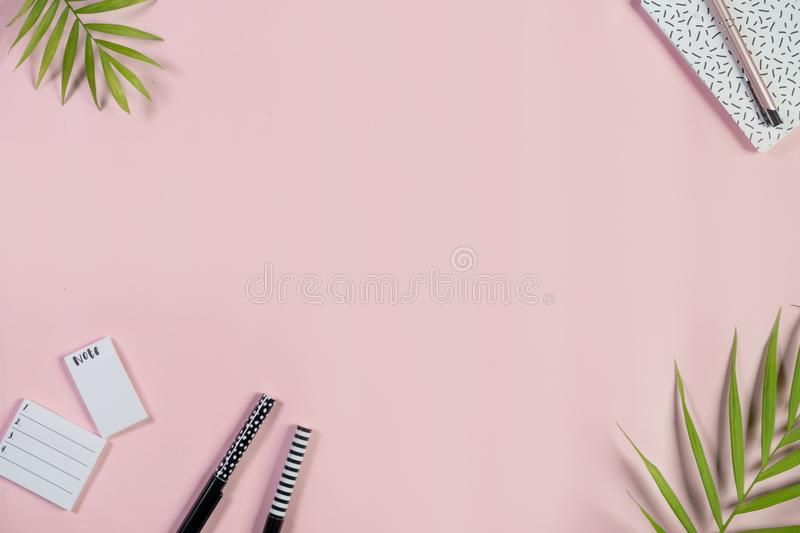 Desk with notepad, to-do list and pens on a light pink background. Top view. stock photography