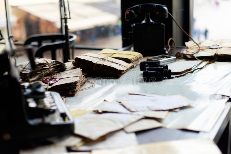 Desk in a old military office. View on a desk in a old military office. A stack of old letters tied with laces, old yellow paper, binoculars, ash tray lying on a stock images