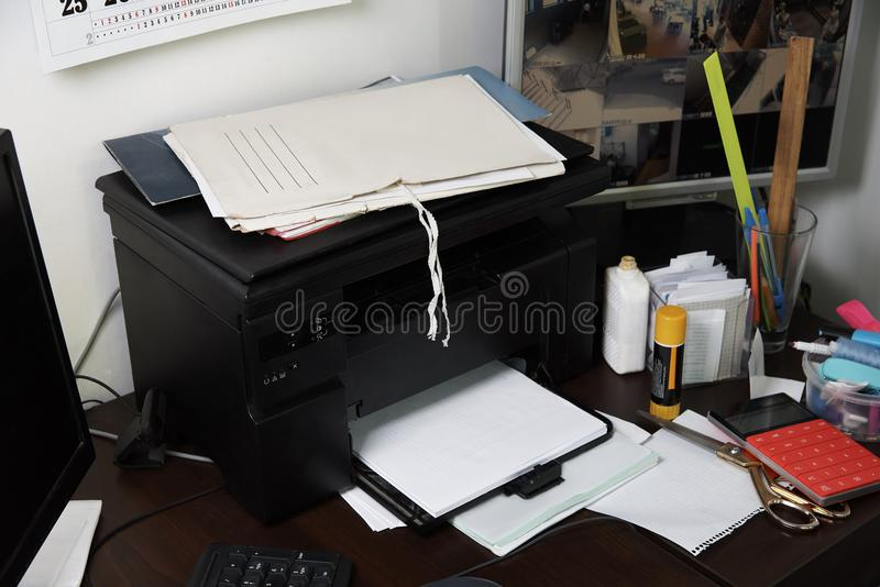 Desk with a printer, papers, computers and office supplies royalty free stock photography