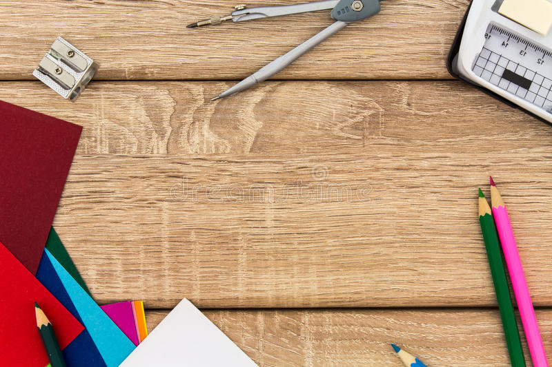 Desk with sharpener, compass, construction paper and colored pencils royalty free stock images