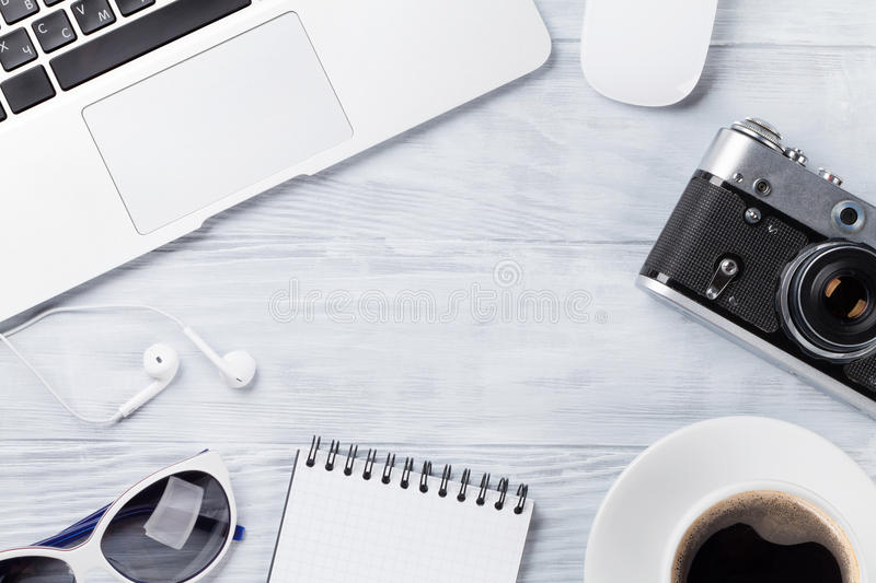 Desk table with laptop, coffee and camera. Desk table with laptop, coffee cup, headphones and camera on wooden table. Workplace. Top view with copy space royalty free stock image