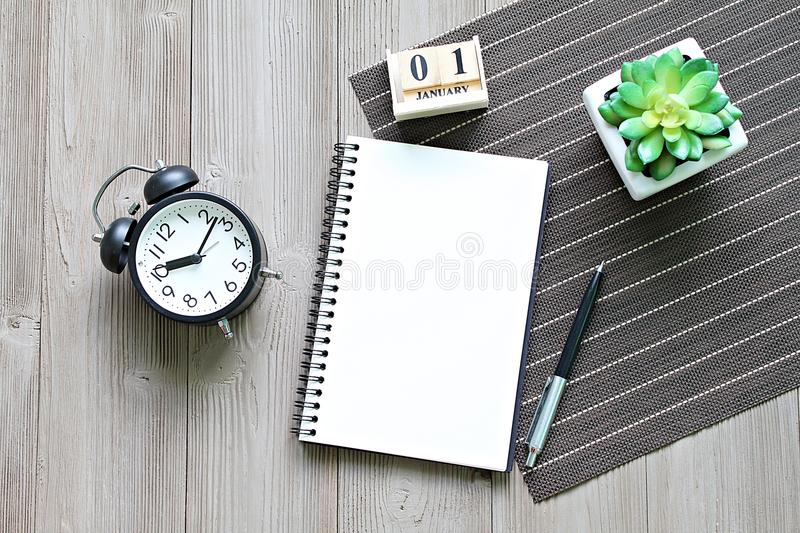Desk table with open notebook paper, cube calendar and clock royalty free stock photo