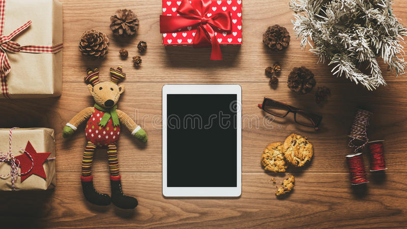 Desk view from above with digital tablet and presents, online shopping retro xmas concept. With copy space stock photography