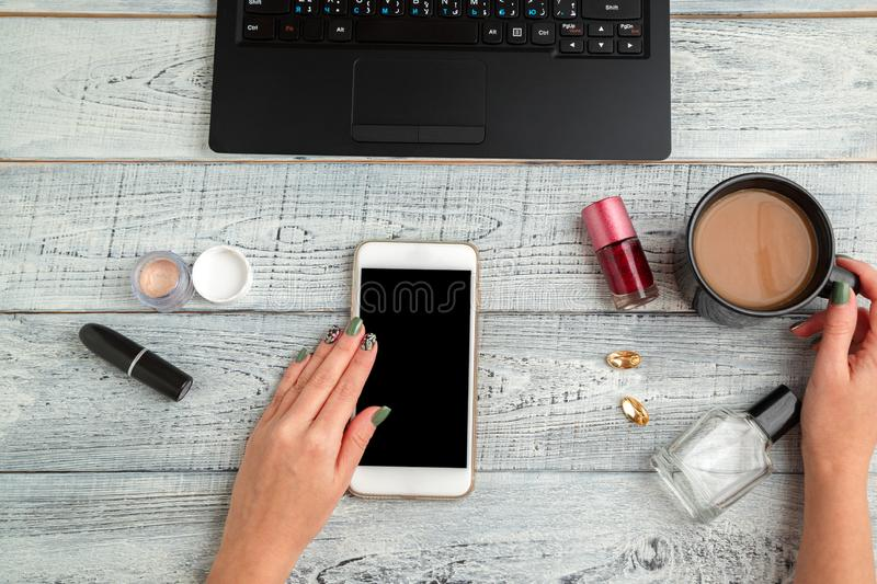 Desk. woman`s workplace. women`s hands,smartphone,laptop,coffee Cup,perfume and cosmetics. the view from the top. flat lay stock photos