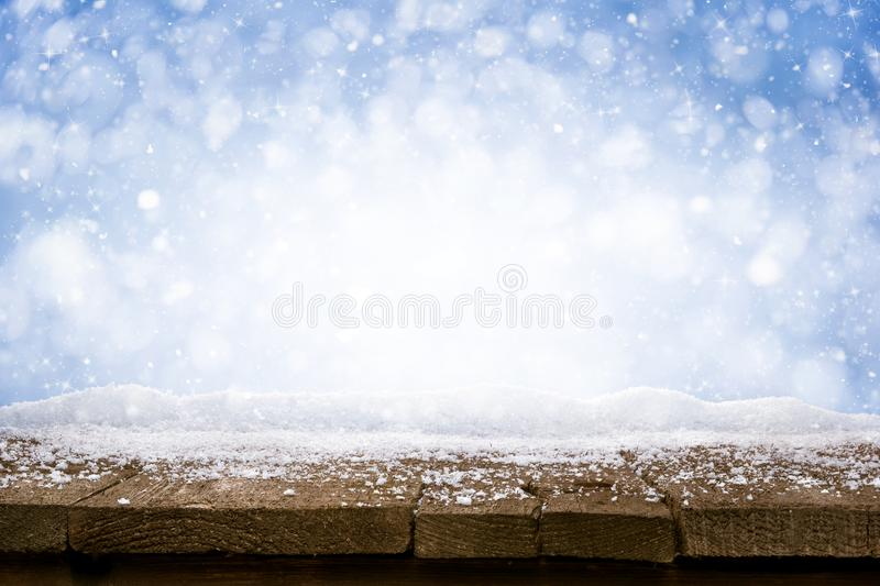 Desk of Wood and Snow - blue blurred background of winter and old shabby table royalty free stock photo