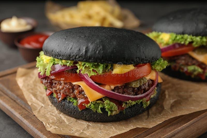 Deska z czarnymi hamburgerami na stole fotografia stock