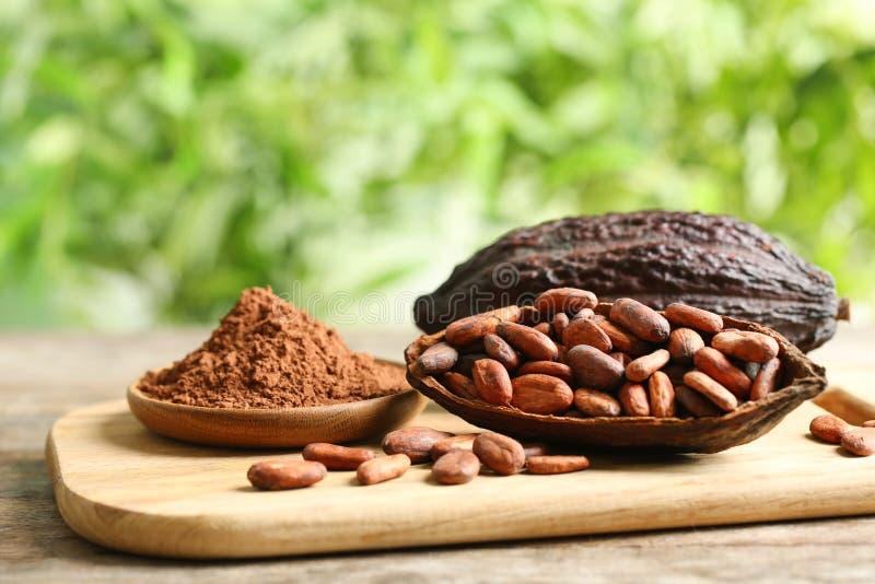 Deska z strąkami, fasolami i proszkiem na stole przeciw zamazanemu tłu kakao, obraz stock
