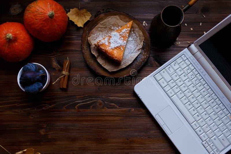 desktop Компьтер-книжка, завтрак, чизкейк тыквы, настольная лампа, тыквы, сливы на деревянном столе Дом, осень, уютная стоковое фото rf