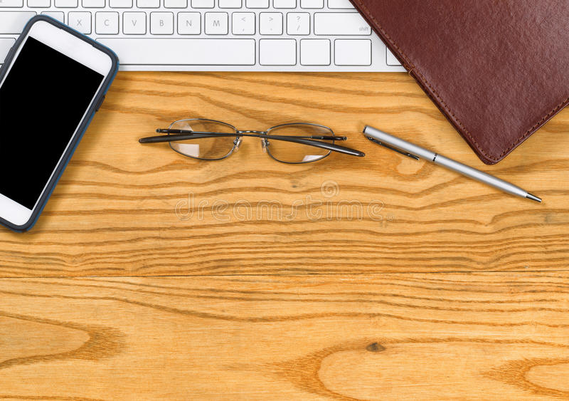 Desktop with basic items for working in office. Top view of computer keyboard notepad binder, reading glasses, pen and cell phone on desktop royalty free stock image