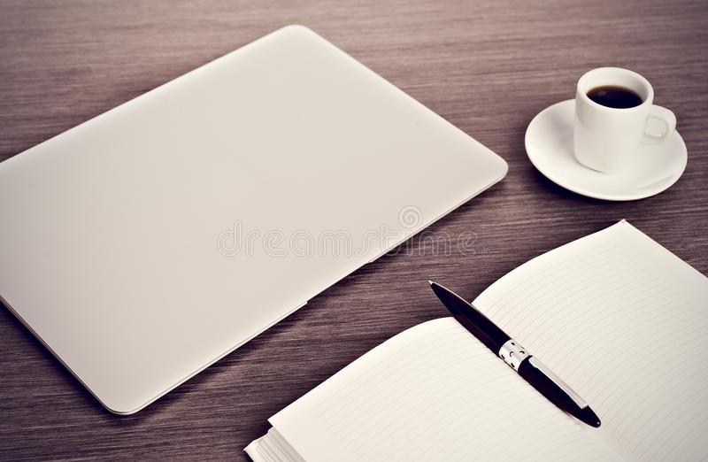 Desktop biuro. Laptop, kawa, notatnik i pióro, zdjęcie stock