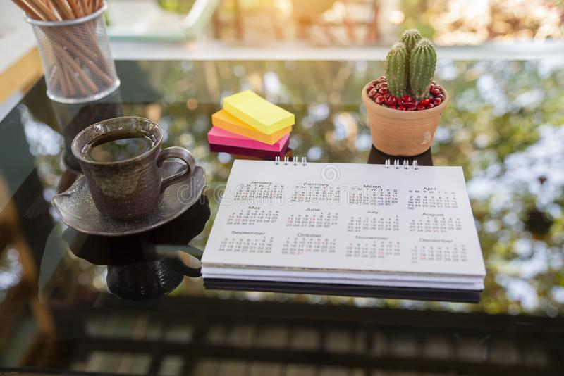 Desktop Calendar pages 2020 on table. With boke background for Planner work on organization,management each date,month year.Cactus pot,and cup of coffee on desk royalty free stock image