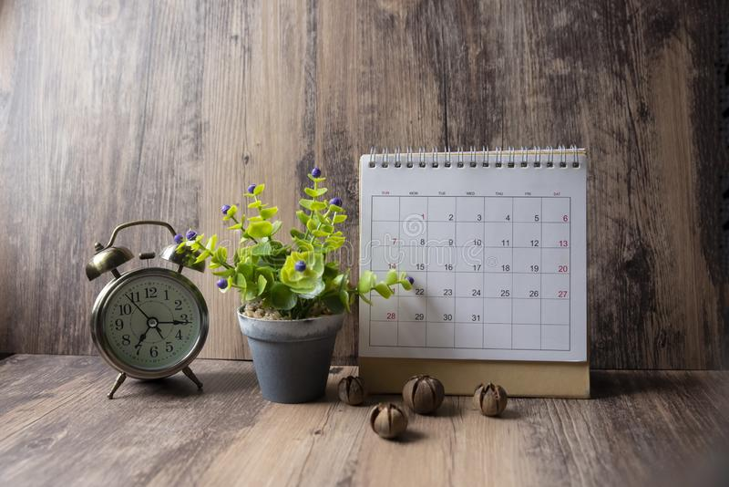 Desktop Calendar 2019 and vintage clock place on wooden office desk.Calender for Planner timetable,agenda appointment,organization. Management on table.Calendar stock photography