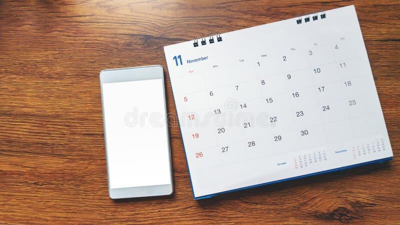 Desktop Calendar 2019 y smartphone en escritorio de madera. tentación, imágenes de archivo libres de regalías
